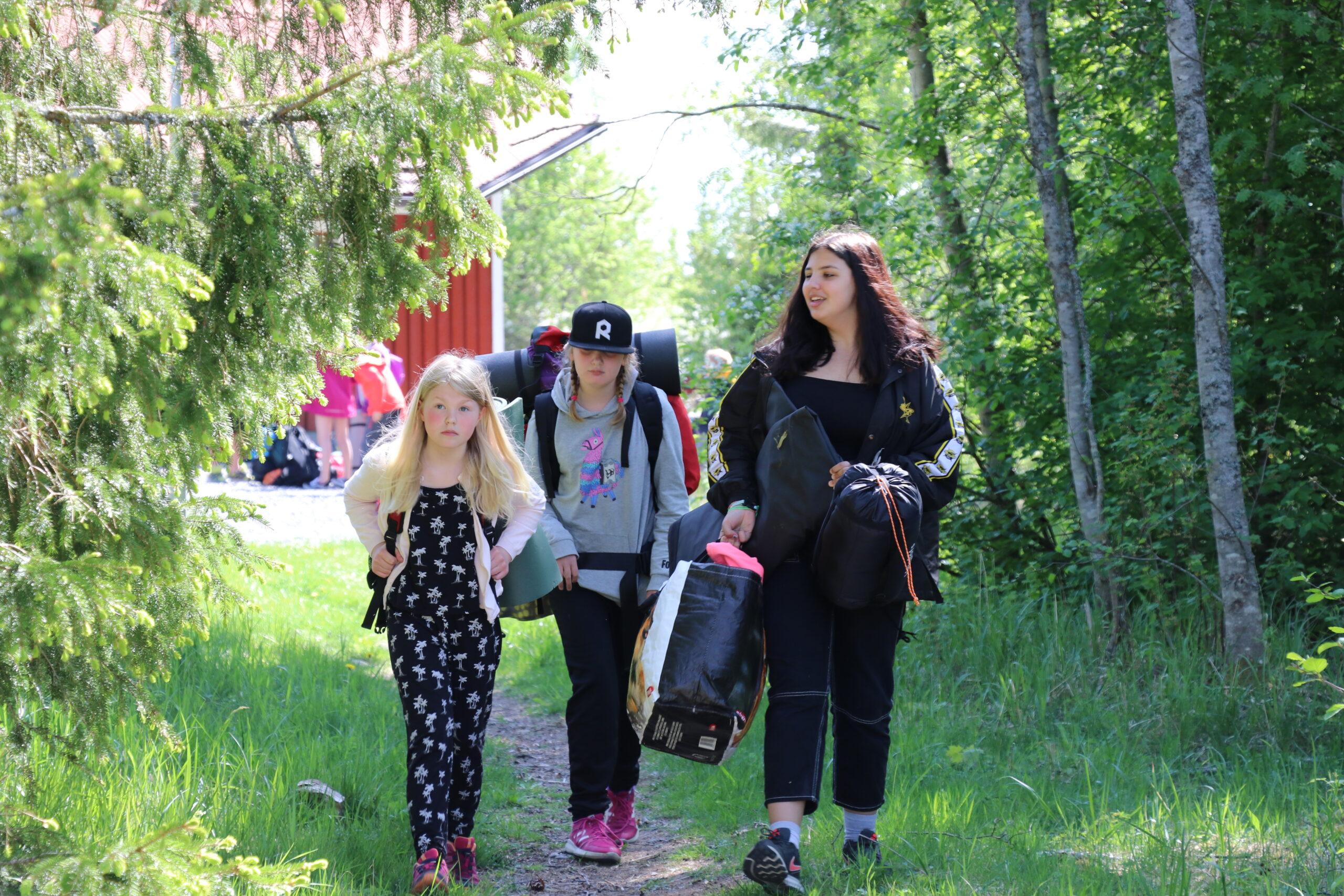 Kolme tyttöä kävelee majoittumaan leirillä