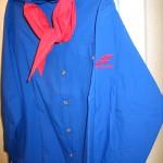Sininen kauluspaita, jonka hihassa punainen Nuoret Kotkat -logo ja kaulassa punainen huivi
