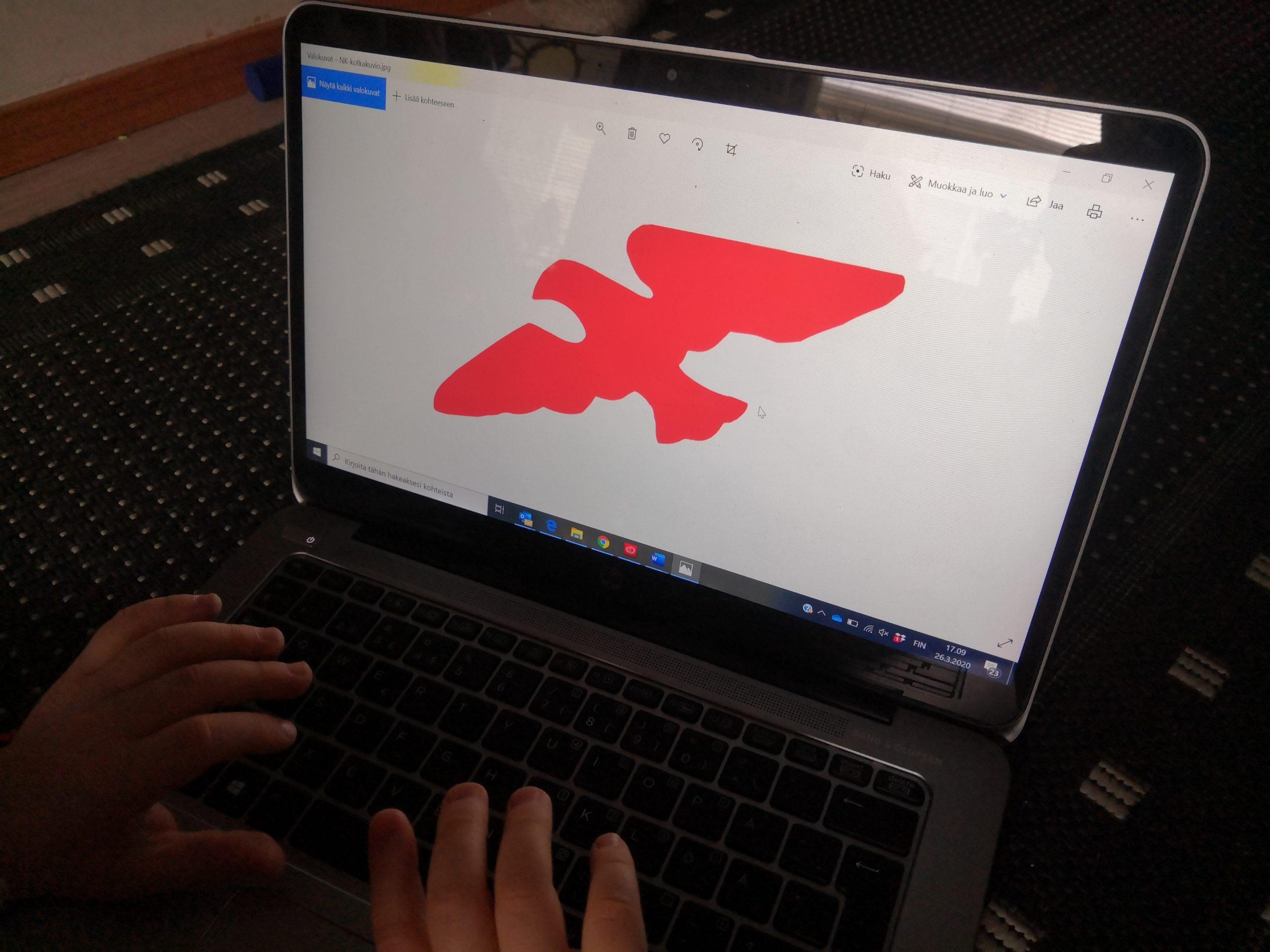 Lapsen kädet tietokoneella, tietokoneen ruudulla Nuorten Kotkien logo