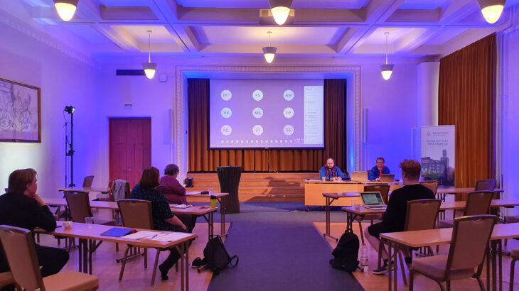Edustajiston kokous käynnissä Paasitornissa, valkokankaalla etäosallistujien nimikirjaimia