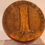 Pyöreä, pronssinen mitali puun kuvalla ja Huominen kasvaa tänään -tekstillä