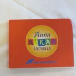 Punainen, pieni muistilappulehtiö sinisellä Nuoret Kotkat -logolla ja Anna aikaa lapselle -painatuksella